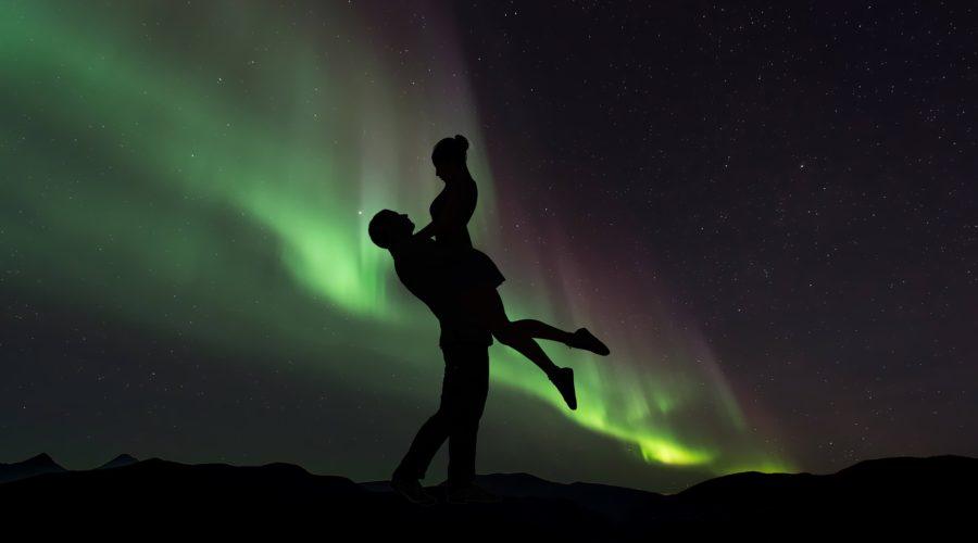 Северное сияние на фоне мужчины и женщины