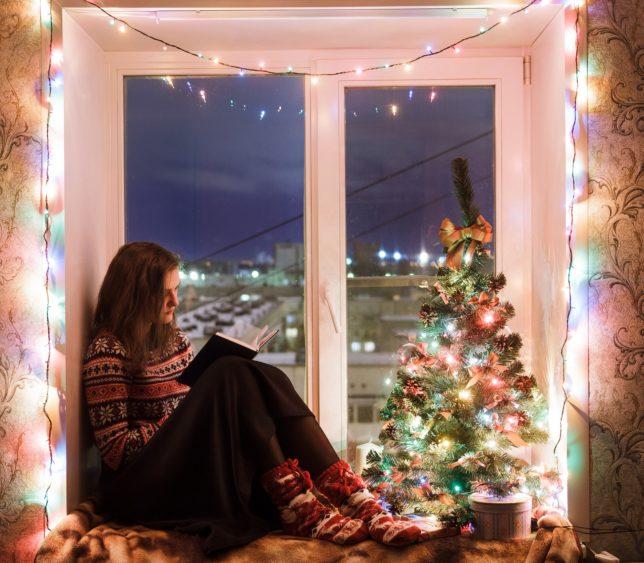 Девушка читает книгу, сидя на подоконнике в плохую погоду