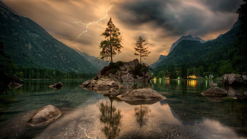 Молния на небе в горах с отражением в озере